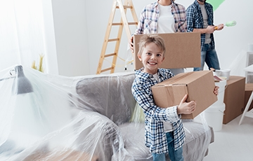 A boy having fun unpacking boxes during a move